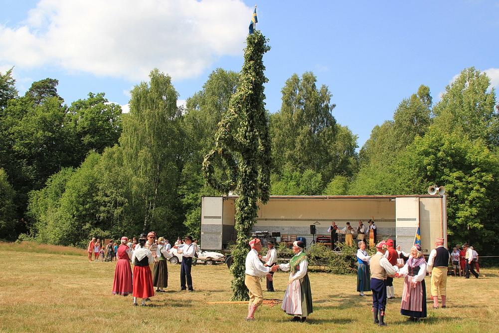 """Die Tanzgruppe tanzt um den Mittsommerbaum. Leider ist das Programm fast 4 Stunden lang - viel zu lange für diese Hitze. Wir beschließen, den Tanz um die """"Stange"""" ausfallen zu lassen und fahren lieber wieder nach Nortorp in den Schatten."""